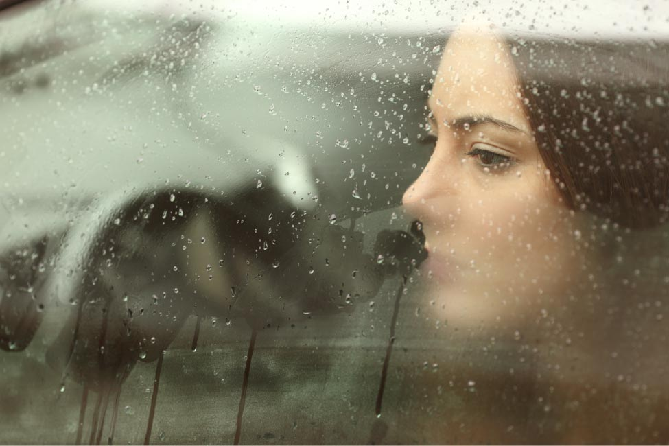 Portrait of a girl by the window right after a rainfall
