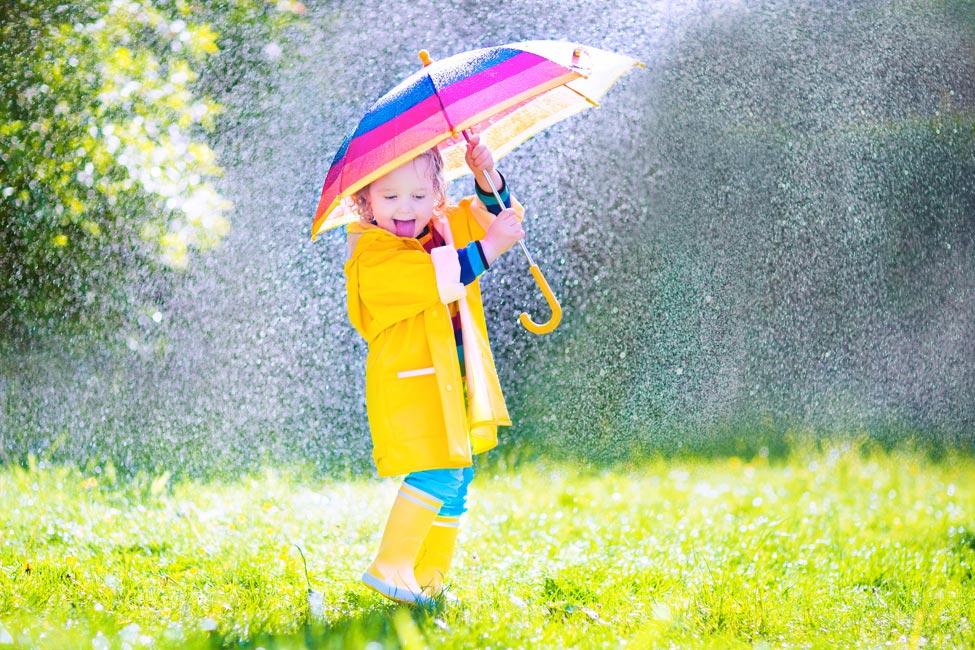 Child holding an umbrella in the rain