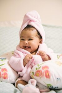 Baby in a spa robe and hair towel laughing