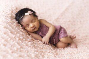 baby lying on pink fleece pad blanket
