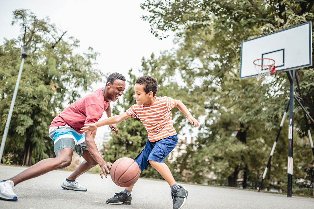 Dad and son playing basketball in their yard