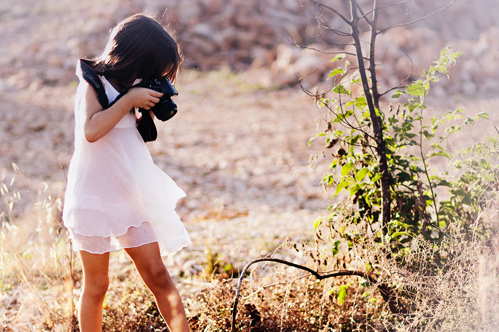 Little girl photographing outdoors
