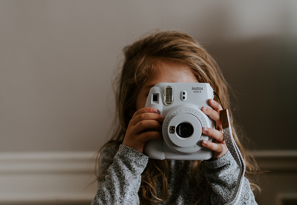 Little girl holding a Fujifilm Instax instant camera