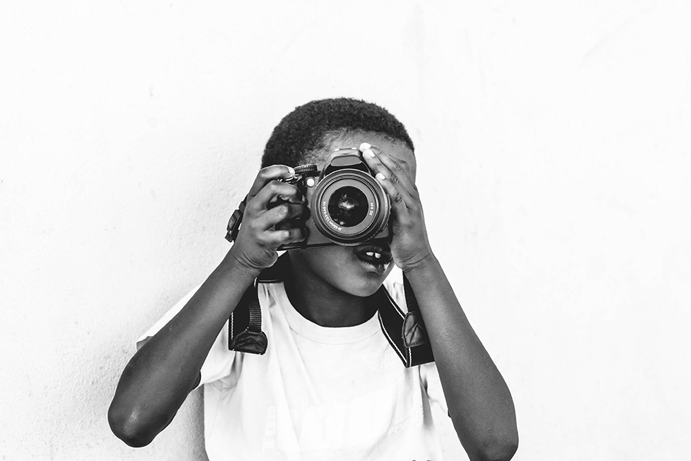 Little boy taking a photo with a DSLR camera