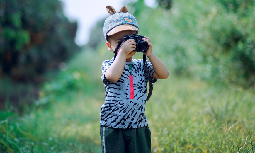 boy taking a photograph in the outdoors