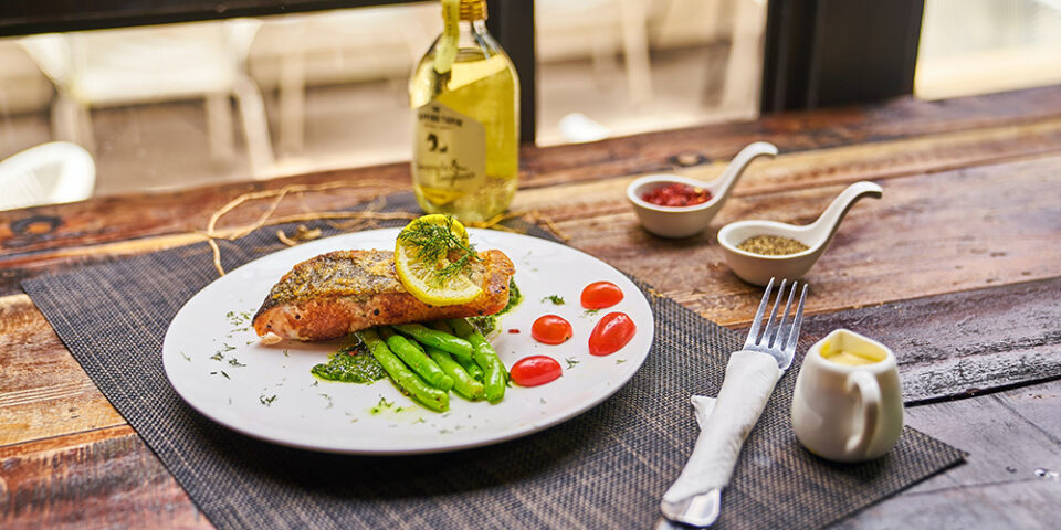 Wooden table with plate of salmon and sides