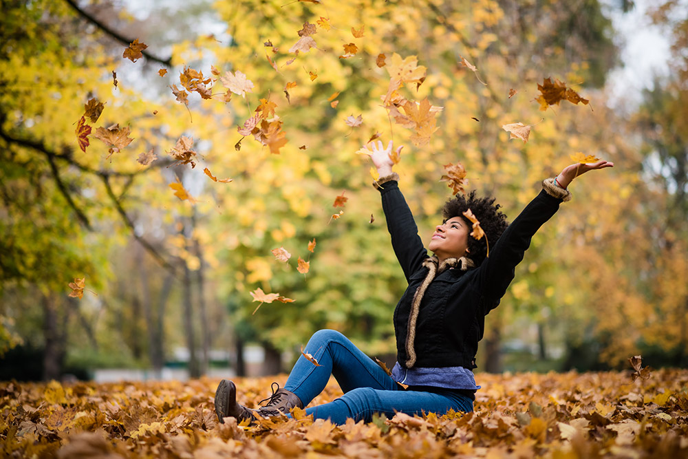 Lady sitting on the ground catching leaves