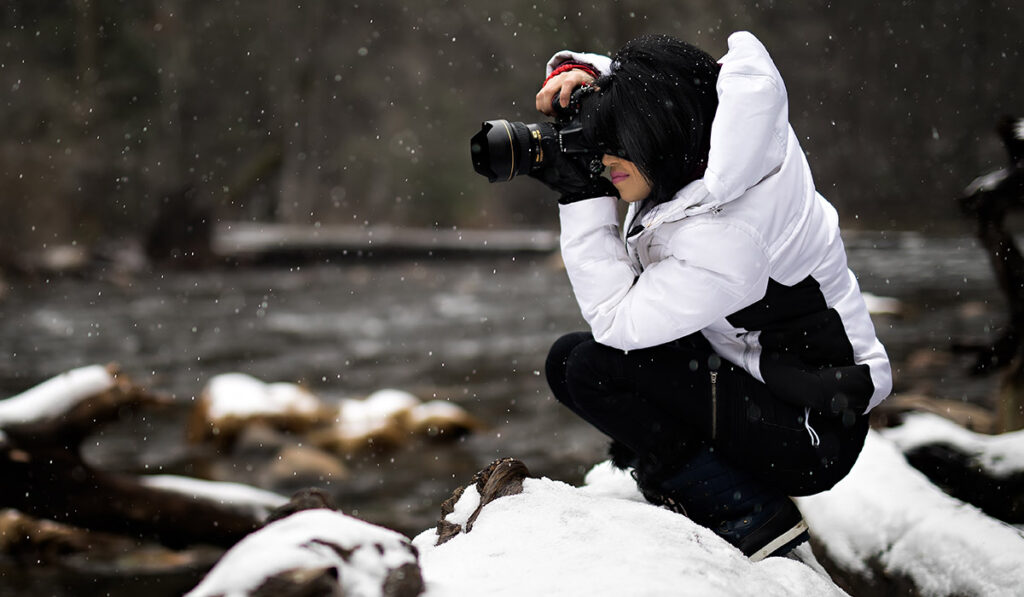 Girl Photographing Outside while Snowing