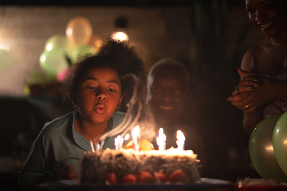 Low light photography - girl blowing out lit birthday candles on a cake
