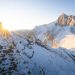 Hiker viewing a mountain sunrise on ridge