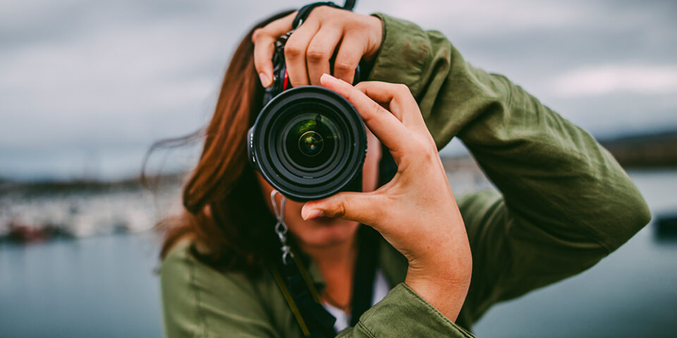Female holding camera taking a photograph
